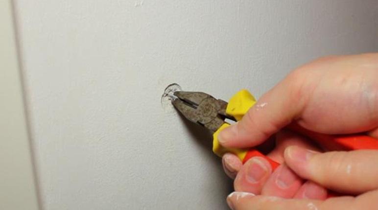 Снятие дюбеля из стены плоскогубцами