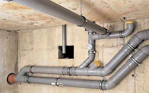 Трубопровод канализации, закрепленный металлическими хомутами с резиновой прокладкой